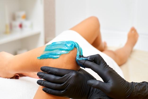 Dosładzanie: koncepcja piękna. procedura usuwania włosów płynny cukier pod ręką w salonie