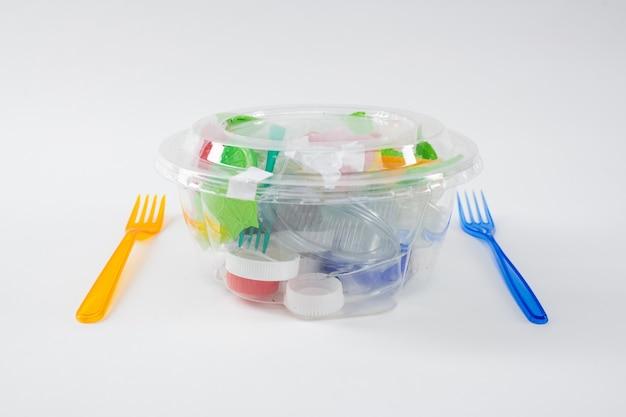 Dosłowny posiłek. szkodliwy stos plastikowych śmieci i kawałków umieszczonych w przezroczystym pojemniku jako instalacja zanieczyszczonego środowiska