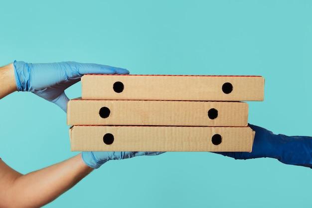 Dostaję dostawę pizzy. pracownik mężczyzna w rękawiczkach, dając kartony kobiecie.