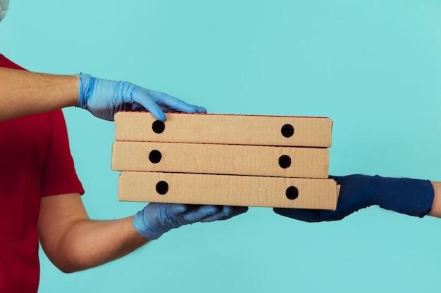 Dostaję pizzę. pracownik mężczyzna w rękawiczkach, dając kobiecie kartony.