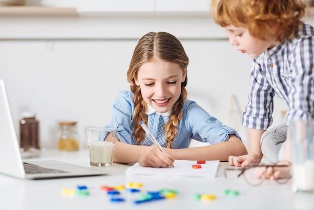 Dostanie a. całkiem mądra, wesoła siostra, korzystając z pomocy swojego młodszego brata, tworząc kreatywną reprezentację jej zadania domowego, podczas gdy on ostrożnie zapisuje formuły swojej siostry