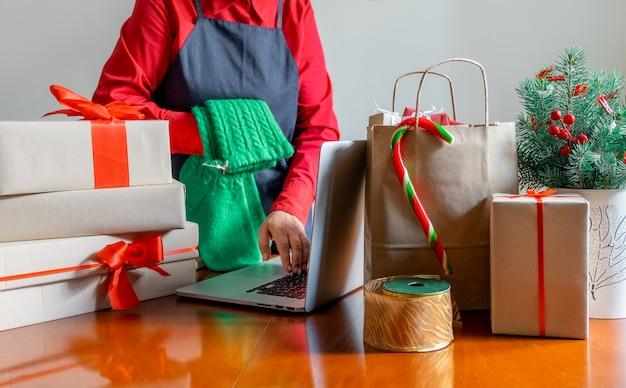 Dostarcz ręce za pomocą laptopa w pobliżu torby do pakowania, pudełek upominkowych i choinki. koncepcja dostawy online.