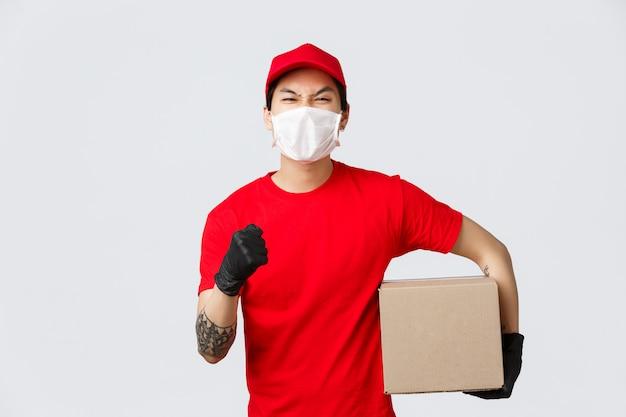 Dostarcz swoje towary bez względu na wszystko. pewny siebie facet dostawy w azji w czerwonej czapce i koszulce w mundurze, podnieś rękę, zachęcaj do złożenia zamówienia, trzymaj pudełko pachage, noś maskę medyczną i rękawiczki