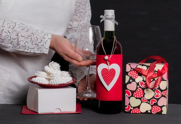 Dostarcz trzymając kieliszek do wina w pobliżu butelki wina z czerwonym sercem walentynkowym, świąteczną torbą i ciastami
