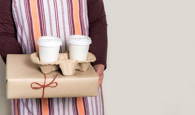 Dostarcz trzymając papierowe pudełka i pojemnik na wynos z dwoma białymi filiżankami kawy.