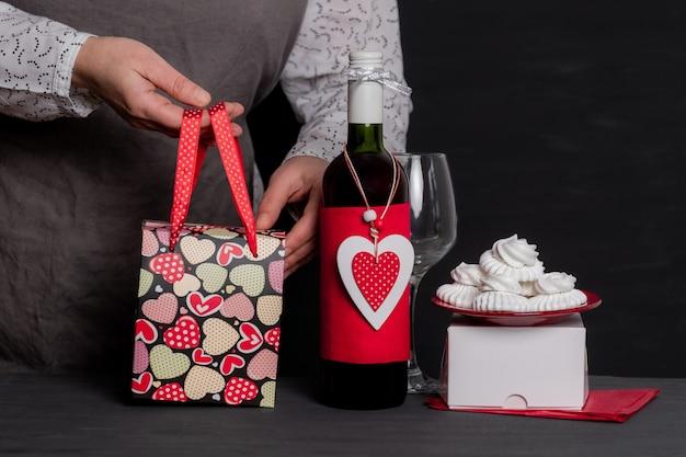 Dostarcz trzymając świąteczną torbę w pobliżu butelki wina z czerwonym sercem walentynkowym i ciastami