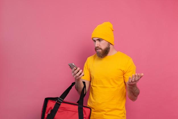 Dostarczając jedzenie z oburzeniem niezadowolony patrząc na telefon na różowo