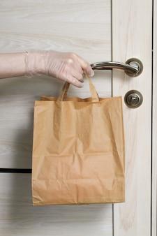 Dostarczanie jedzenia w papierowej torbie podczas wybuchu covid 19. kobieta wolontariuszka trzyma torbę spożywczą w pobliżu drzwi. środki ostrożności przeciwko covid-19.