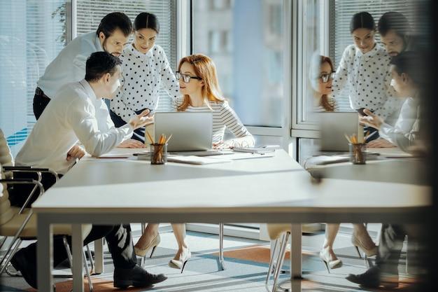 Dostarczanie opinii. sympatyczni młodzi pracownicy oglądający prezentację projektu na laptopie swojego szefa i dzielący się swoimi opiniami na jego temat