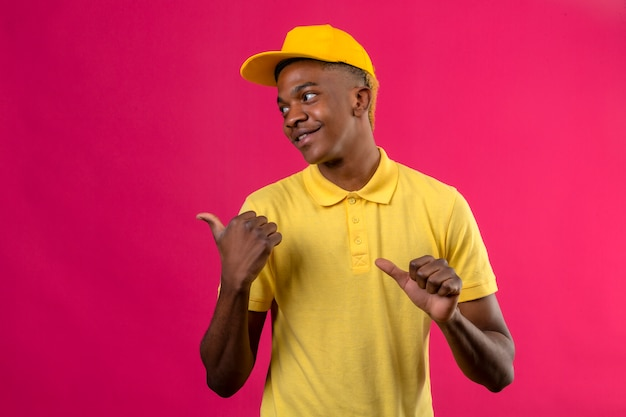 Dostawa afroamerykanin mężczyzna w żółtej koszulce polo i czapce patrząc na bok, wskazując na bok z kciukami uśmiechnięty przyjazny stojący na różowo