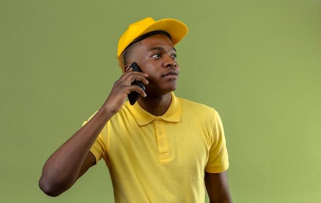 Dostawa afroamerykanin mężczyzna w żółtej koszulce polo i czapce rozmawia przez telefon komórkowy patrząc na bok z poważną twarzą na zielono