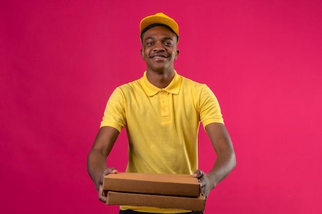 Dostawa afroamerykanin mężczyzna w żółtej koszulce polo i czapce stojącej z pudełkami po pizzy w rękach wyciągając uśmiechnięty przyjazny na różowo