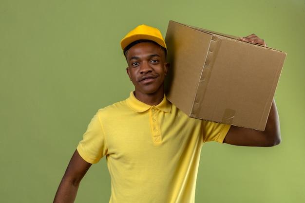 Dostawa afroamerykanin mężczyzna w żółtej koszulce polo i czapce stojącej z tekturowym pudełkiem na ramieniu, patrząc pewnie na zielono