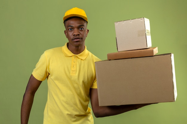 Dostawa afroamerykanin mężczyzna w żółtej koszulce polo i czapce stojącej ze stosem kartonów, patrząc pewnie na zielono