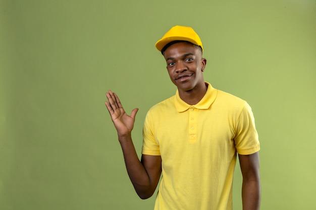 Dostawa afroamerykanin mężczyzna w żółtej koszulce polo i czapce uśmiechnięty przyjazny z podniesioną ręką stojącą na zielono