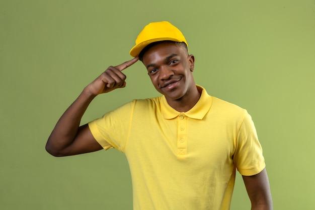 Dostawa afroamerykanin mężczyzna w żółtej koszulce polo i czapce wskazujący świątynię wyglądającą na pewną siebie dumną skoncentrowaną na zadaniu stojącym na zielono