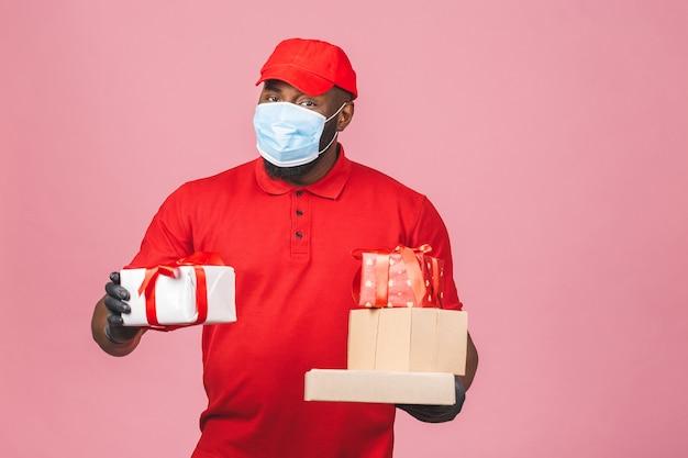 Dostawa afroamerykanin pracownik mężczyzna w czerwonej czapce pusty t-shirt jednolita maska na twarz rękawiczki trzymają puste kartonowe pudełko