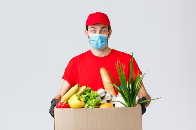 Dostawa artykułów spożywczych i paczek, covid-19, koncepcja kwarantanny i zakupów. kurier z paczką żywnościową przywozi towar do domu klienta, dostawę bezdotykową podczas koronawirusa, nosi maskę na twarz i rękawiczki
