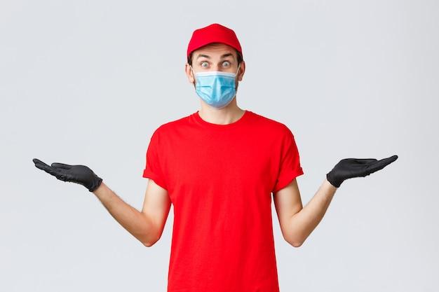 Dostawa artykułów spożywczych i paczek, covid-19, koncepcja kwarantanny i zakupów. zaskoczony kurier w czerwonym mundurze, rękawiczkach i masce na twarz trzymający się bokiem za ręce z transparentem lub promocją firmy przewozowej