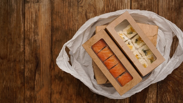 Dostawa azjatyckiego jedzenia. jedzenie w pojemnikach oraz w opakowaniu na drewnianym tle. japońskie opakowania do żywności i sushi.