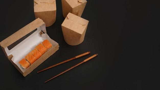 Dostawa azjatyckiego jedzenia. opakowania na sushi i woki. jedzenie w papierowych pojemnikach na czarnym tle. otwarte opakowanie z roladkami z łososia