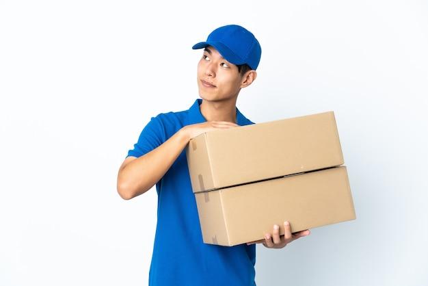 Dostawa chińczyk na białym tle na białej ścianie patrząc uśmiechnięty