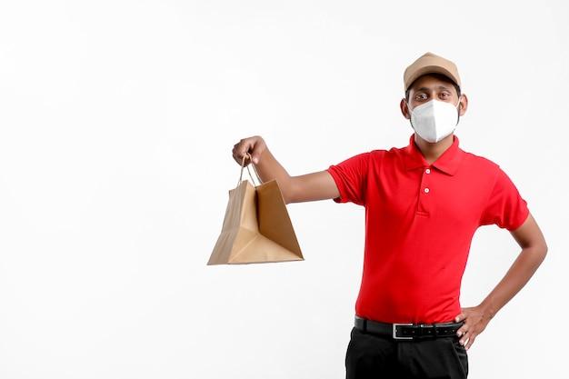 Dostawa człowiek nosi maskę medyczną i trzymaj pudełko w rękach. dostawca. koncepcja bezpiecznej dostawy.
