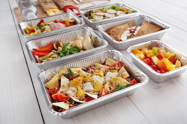 Dostawa dań do restauracji. jedzenie na wynos w pudełkach foliowych. sałatka z dorszem, kiełkami pszenicy i chrupiącymi kawałkami tortilli na białym drewnie