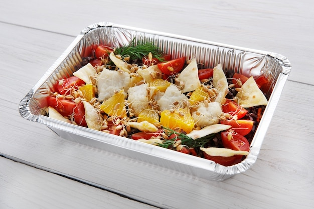 Dostawa dań do restauracji. jedzenie na wynos w pudełkach foliowych. sałatka z kiełkami pszenicy i chrupiącymi kawałkami tortilli na białym drewnie