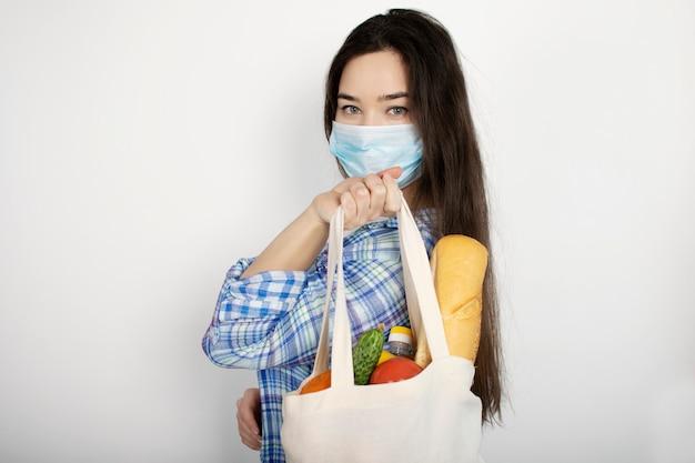 Dostawa do domu podczas koronawirusa, epidemii wirusowych i pandemii. dziewczyna w błękitnych rękawiczkach trzyma torbę z produktami na białym odosobnionym tle. covid-19