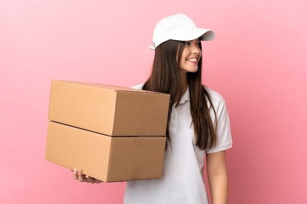 Dostawa dziewczyna na białym tle różowa ściana patrząc w bok i uśmiechnięta