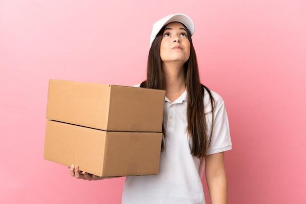Dostawa dziewczyna na odosobnionej różowej ścianie i patrząc w górę