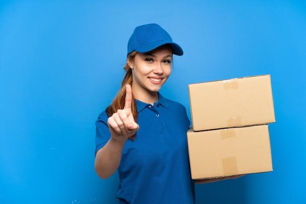 Dostawa dziewczyna nad odosobnioną niebieską ścianą pokazującą i unoszącą palec