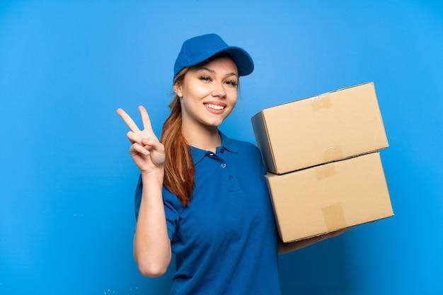 Dostawa dziewczyna nad odosobnioną niebieską ścianą uśmiecha się i pokazuje znak zwycięstwa