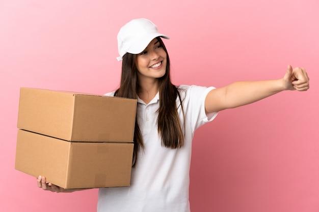 Dostawa dziewczyna nad odosobnioną różową ścianą, dając gest kciuka w górę