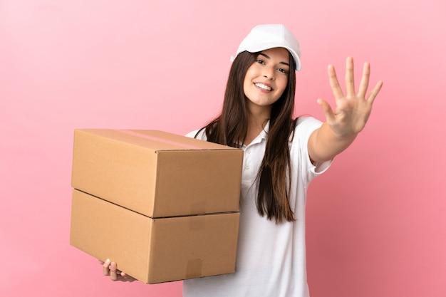 Dostawa dziewczyna nad odosobnioną różową ścianą, licząc pięć palcami