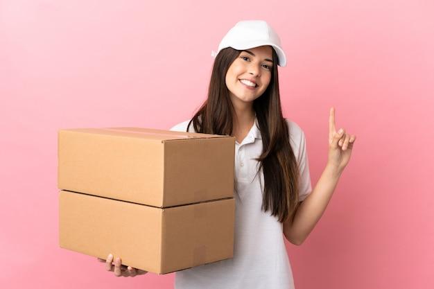 Dostawa dziewczyna nad odosobnioną różową ścianą pokazującą i unoszącą palec na znak najlepszych