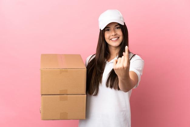Dostawa dziewczyna nad odosobnioną różową ścianą robi nadchodzący gest