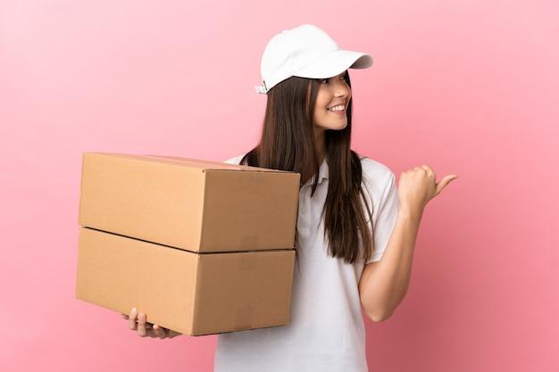 Dostawa dziewczyna nad odosobnioną różową ścianą skierowaną w bok, aby zaprezentować produkt