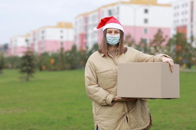 Dostawa dziewczyna w czerwonej czapce świętego mikołaja i medycznej masce ochronnej trzyma duże pudełko na zewnątrz.