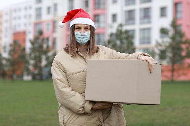Dostawa dziewczyna w czerwonej czapce świętego mikołaja i medycznej masce ochronnej trzyma duże pudełko na zewnątrz