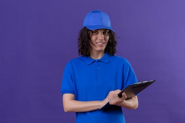 Dostawa dziewczyna w niebieskim mundurze i czapce trzymając schowek z przyjaznym uśmiechem na stojąco