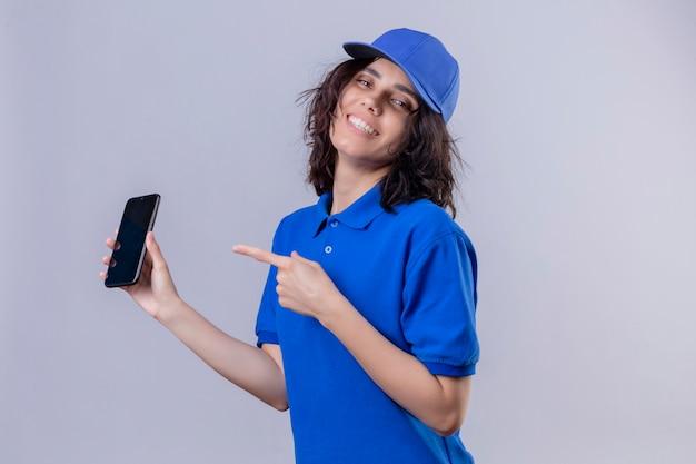 Dostawa dziewczyna w niebieskim mundurze i czapce, trzymając telefon komórkowy i wskazując palcem wskazującym na to, uśmiechając się wesoło stojąc