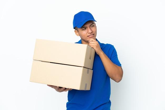 Dostawa ekwadorski mężczyzna na białym tle na białej ścianie, patrząc z boku i uśmiechnięty