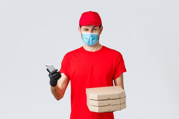 Dostawa jedzenia, aplikacja, zakupy zbliżeniowe online i koncepcja covid-19. kurier w czerwonym mundurze, masce i rękawiczkach, mruga do klienta, informuje o bonusach, specjalnych zniżkach na pizzę, trzymaj telefon