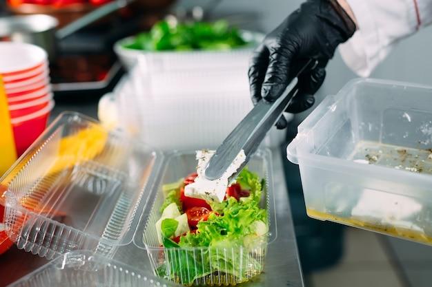 Dostawa jedzenia do restauracji. szef kuchni przygotowuje potrawy w restauracji i pakuje je w dania jednorazowe.