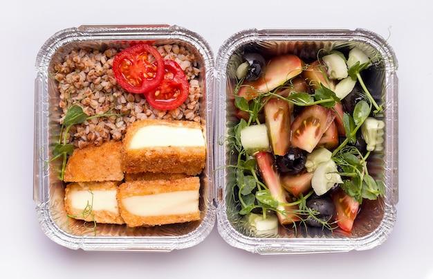 Dostawa jedzenia. kasza gryczana z warzywami i serem oraz surówka z mikro zieleniną, oliwkami i pomidorem. zbliżenie, widok z góry