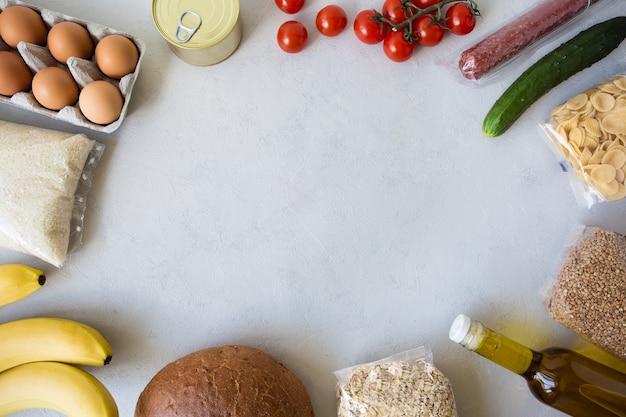 Dostawa jedzenia online ze sklepu. zestaw widok z góry żywności z ramką na miejsce na tekst na szarym tle.