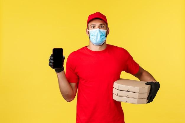 Dostawa jedzenia, śledzenie zamówień, koncepcja covid-19 i samodzielna kwarantanna. entuzjastyczny kurier w czerwonym mundurze, masce medycznej i rękawiczkach, pokazujący aplikację do zamawiania pizzy, aplikację track na smartfonie