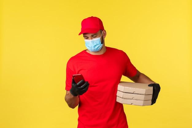 Dostawa jedzenia, śledzenie zamówień, koncepcja covid-19 i samodzielna kwarantanna. kurier sprawdzający adres klienta na telefonie, przynosząc zamówienie na pizzę, dzwoniąc do klienta, stojąc na żółtym tle